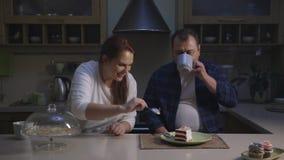 Família caucasiano engraçada que está próximo com tabela e que termina um bolo de aniversário vídeos de arquivo