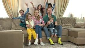 Família caucasiano feliz que olha a tevê