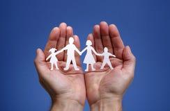 Família chain de papel protegida nas mãos colocadas Imagem de Stock Royalty Free