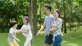 Família chinesa que aprecia a atividade do fim de semana no parque no verão imagem de stock