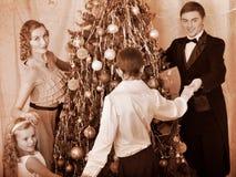 Família com a árvore de Natal da dança redonda das crianças. Foto de Stock