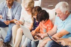 Família com as avós que usam a tecnologia ao sentar-se no sofá Fotografia de Stock Royalty Free