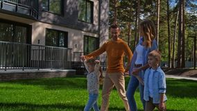 Família com as crianças que andam no parque perto da casa mo lento vídeos de arquivo