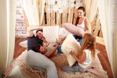 Família com as crianças que jogam com descansos em casa na cama Imagem de Stock Royalty Free