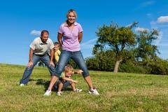 Família com as crianças que jogam em um prado Imagens de Stock Royalty Free