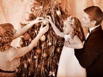 Família com as crianças que vestem a árvore de Natal. Imagens de Stock
