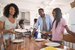 Família com as filhas adolescentes que colocam a tabela para a refeição na cozinha fotografia de stock