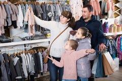 Família com as filhas que mostram suas compras no cl dos children's imagem de stock royalty free