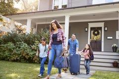 Família com a bagagem que sae da casa para férias foto de stock