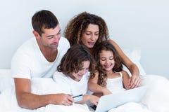 Família com cartão de crédito que compra em linha na cama imagem de stock