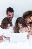 Família com cartão de crédito que compra em linha na cama imagem de stock royalty free