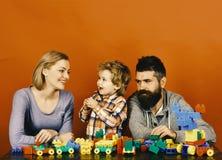 Família com construção de sorriso das caras fora dos blocos coloridos da construção Imagens de Stock Royalty Free