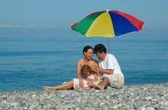 Família com criança em uma praia Foto de Stock Royalty Free