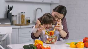 Família com a criança especial das necessidades que cozinha na cozinha vídeos de arquivo