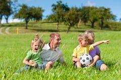 Família com crianças e futebol em um prado Foto de Stock Royalty Free