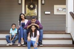 Família com crianças Sit On Steps Leading Up ao patamar da casa fotos de stock