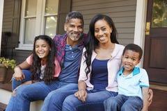 Família com crianças Sit On Steps Leading Up ao patamar da casa fotografia de stock royalty free