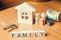 A família com dinheiro está estando perto de sua casa conceito da vida da riqueza e um feliz bem-dotado inscription imagem de stock royalty free