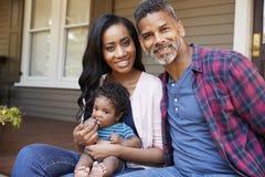 Família com filho Sit On Steps Leading Up do bebê ao patamar da casa imagens de stock royalty free