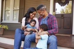 Família com filho Sit On Steps Leading Up do bebê ao patamar da casa foto de stock royalty free