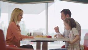 A família com menina come no café no posto de gasolina video estoque
