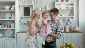 Família com o bebê que come o café da manhã na cozinha junto, povos americanos felizes filme