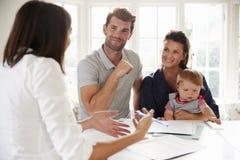 Família com o bebê que encontra o conselheiro financeiro em casa imagem de stock royalty free