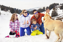 Família com o cão que tem o divertimento na neve foto de stock royalty free