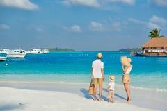 Família com o menino da criança de três anos na praia fotografia de stock