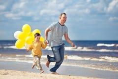 Família com os balões amarelos que jogam na praia Fotos de Stock