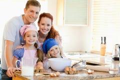 Família com os ingredientes do cozimento atrás do contador de cozinha imagem de stock