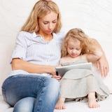 Família com a tabuleta no sofá em casa Foto de Stock Royalty Free