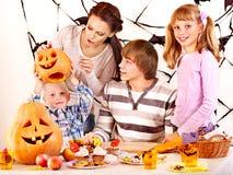A família com terra arrendada da criança faz a abóbora cinzelada. Imagens de Stock Royalty Free