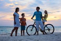 Família com uma bicicleta na praia tropical fotografia de stock