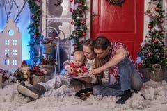 Família com uma criança pequena que senta-se na neve perto da porta imagem de stock royalty free