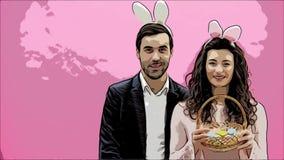 A família comemora o dia da Páscoa Pares felizes com orelhas do coelho Boas festas Acople ovos de pintura para a Páscoa decorar video estoque