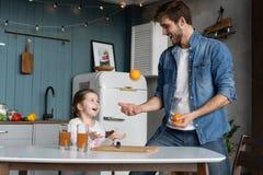 Família, comer e conceito dos povos - pai feliz e filha que comem o café da manhã em casa fotos de stock