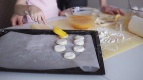 Família, cozimento e conceito dos povos - mãe feliz e sua cozinha pequena da filha em casa aplicar cookies com chicoteado video estoque