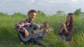 A família criativa, paizinho de riso feliz ensina o filho aos jogos amarrou o quando do instrumento quando o mum aplaudir e rir o video estoque