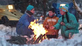 Família da floresta do inverno que senta-se nas madeiras pelo fogo, falando e fritando salsichas filme