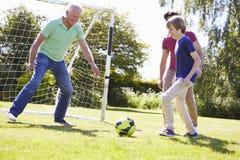 Família da geração do homem três que joga o futebol junto fotos de stock royalty free