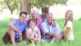 Família da Multi-geração que senta-se no campo junto video estoque