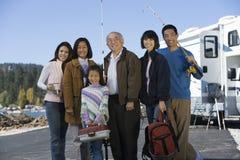 família da Três-geração que guardara polos de pesca pelo rv no lago Fotos de Stock