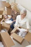 Família das gerações que desembala as caixas que movem a casa Fotos de Stock