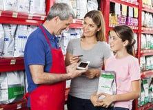Família de Accepting Payment From do vendedor na loja de animais de estimação fotos de stock