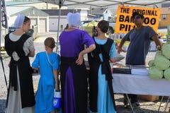 Família de Amish que está na tabela que inspeciona bens que puderam querer comprar, Dragon Farmers Market verde, Ephrata, PA, 201 fotografia de stock