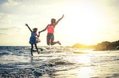Família de amor feliz da mãe e da filha que saltam na água no por do sol na praia - mamã com sua criança que tem o divertimento j foto de stock