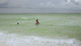 Família de amor feliz do pai, da mãe e do filho tendo o divertimento na água do mar no verão, no curso, nas férias e na família d filme
