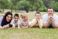 Família de cinco alegre que encontram-se no gramado Fotografia de Stock Royalty Free
