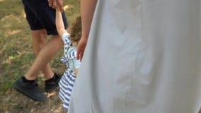 Família de mãos dadas, criança adotada sendo apoiada por pais amorosos video estoque